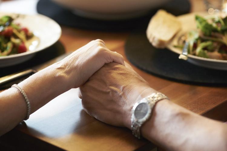 Elderly Couple Holding Hands at Dinner