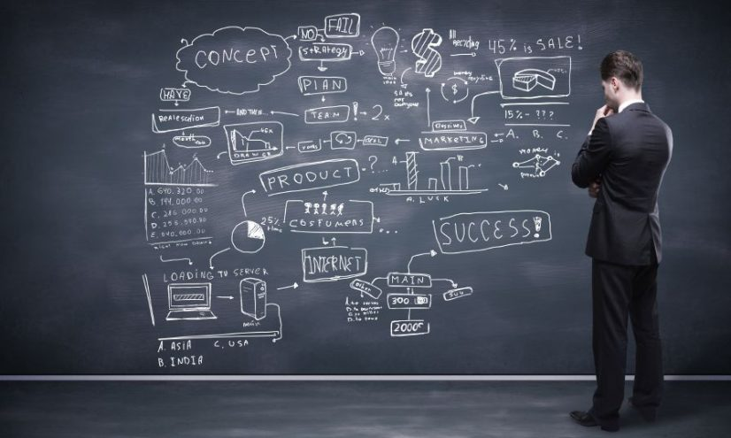 Businessman Looking at Concept on Blackboard